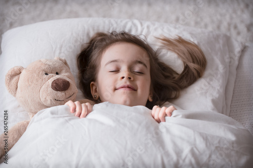 Little cute girl in bed with toy Wallpaper Mural