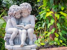 Cupid Sculpture In The Garden.