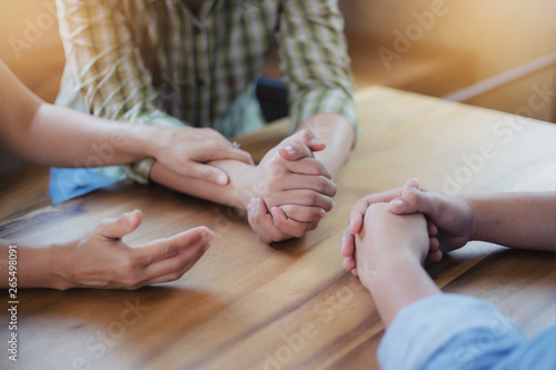 Two Christian people are praying for young man friends on wood table at church p Canvas Print