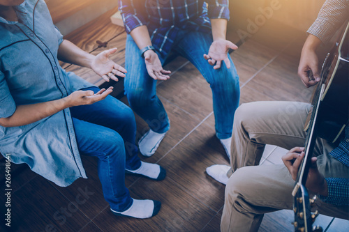 Stampa su Tela  Group of  man and woman friends sitting on wooden chair while praise and worship God  by playing guitar and sing a song together in home office, Christian background small fellowship meeting concept
