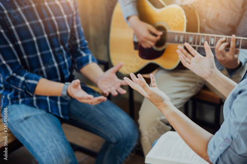 Group of  man and woman friends sitting on wooden chair while praise and worship God  by playing guitar and sing a song together in home office, Christian background small fellowship meeting concept Canvas-taulu