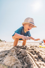 Low Angle Of Toddler Boy Playing On A Sandy Beach