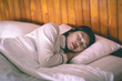 Beautiful Attractive Asian woman wearing Pajamas sleep close her eyes smile sleep and sweet dream on bed in bedroom in the morning feeling so relax and comfortable,Healthcare and Sleep Concept