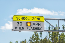 Public School Zone Sign On Road With 30 Miles Per Hour When Flashing Text In Naples, Florida During Day