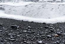 Black Volcanic Stones On Sand Beach In Reynisfjara, Iceland With Water Waves Crashing On Shore To Shiny Wet Rocks In Vik