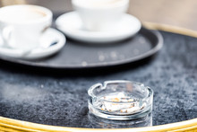 Closeup Of Table With Used Coffee Or Afternoon Tea Cup In Outdoor Cafe With Nobody In London, UK And Ashtray With Cigarettes