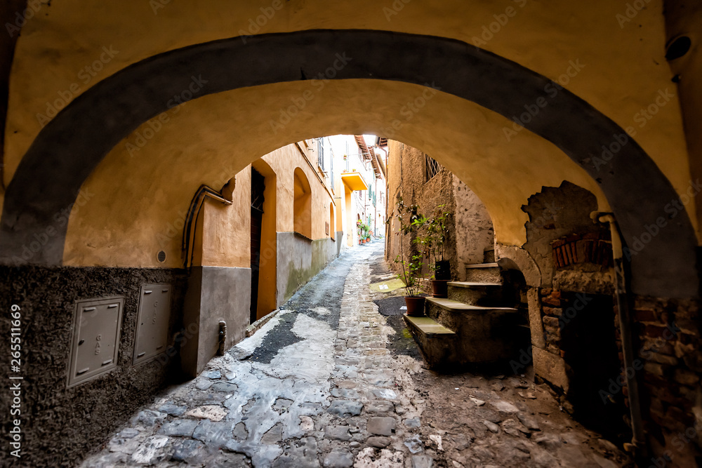 Chiusi, Italy street in small historic town village in Umbria during day with nobody orange colorful walls and arch path