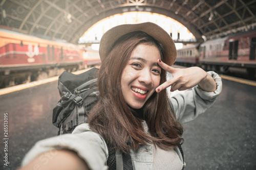 Woman Traveler with backpack traveling taking picture self portrait with smartphone on her summer vacation Wallpaper Mural