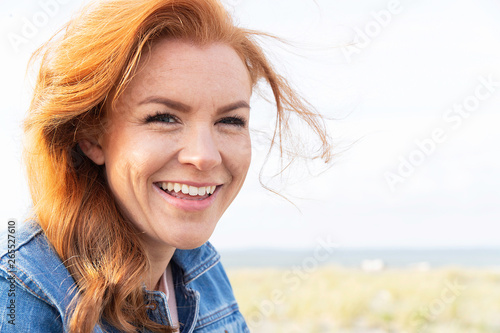 Aluminium Prints Equestrian Friendly woman with red hair at the beach