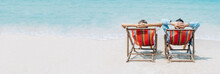Panoramic Banner Image Of A Sweet Couple Whilst Sitting On Deck Chairs A Blue Sky On A Beach Vacation, Honeymoon Trip. Wide Crop