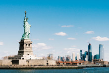 Statue Of Liberty On Sunny Day With New York City Manhattan Island In Background. America Cityscape, United States Nation Symbol, Travel Destination Or Tourist Attraction Concept
