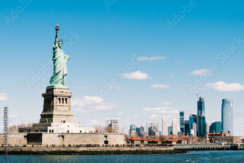 Poster New York Statue of Liberty on sunny day with New York city Manhattan island in background. America cityscape, United States nation symbol, travel destination or tourist attraction concept