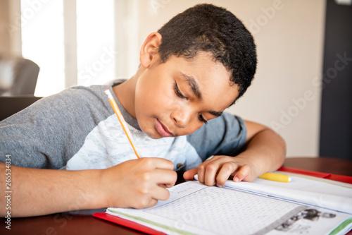 Fotografie, Obraz  A male black child doing homework at home