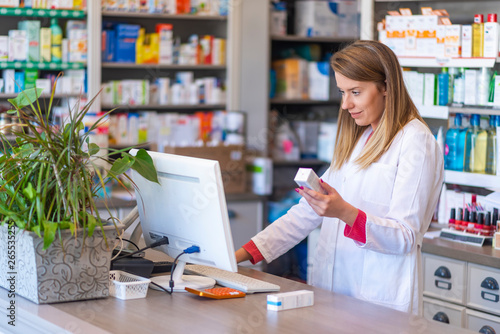 Photo sur Toile Pharmacie Female pharmacist working in chemist shop or pharmacy. Pharmacist using the computer at the pharmacy. Portrait of young female pharmacist holding medication while using computer at pharmacy counter