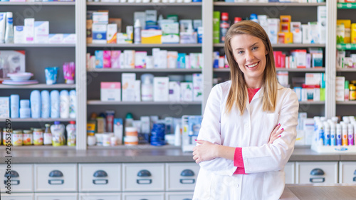 Papiers peints Pharmacie Portrait of a smiling pharmacist with arms crossed at modern pharmacy. Beautiful woman wearing in white lab coat working in drugstore.