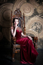 Queen In Red Dress Sitting On Throne. Symbol Of Power