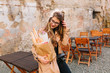 Nice shy girl with long hair looks at the bakery bag standing in outdoor restaraunt in front of old building. Pretty stylish lady in glasses straightening her hair and posing after food shopping.