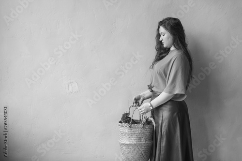 Fotografija  Young beautiful long haired girl carrying chicken in straw basket on textured wall background