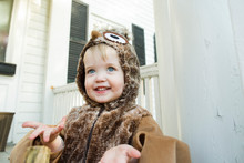 Blue Eyed Toddler Holds Out Hands Smiling While Dressing Up As An Owl