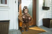 Boy In Halloween Costume Standing In Front Of Doorway