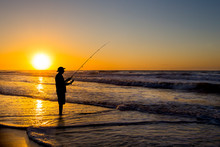 Silhouette Of Man Fishing In Waves On Beach At Sunset