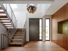 Plank Floor And Walnut Wall Covering In Home Near Staircase