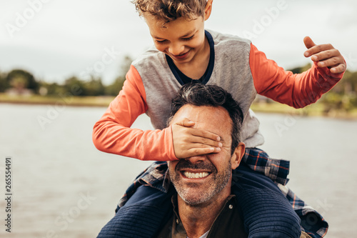 Father and son playing near the lake Poster Mural XXL