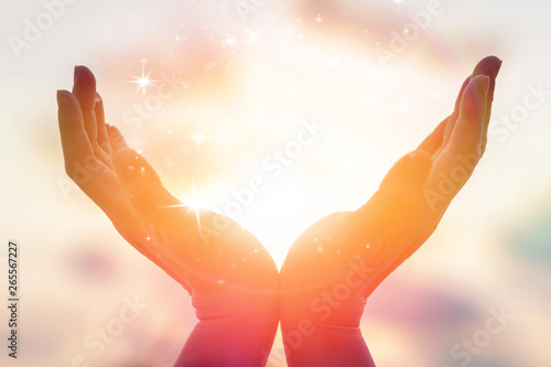 Obraz na plátně Silhouette of female hands holding sunset or sunrise for people energy and seren