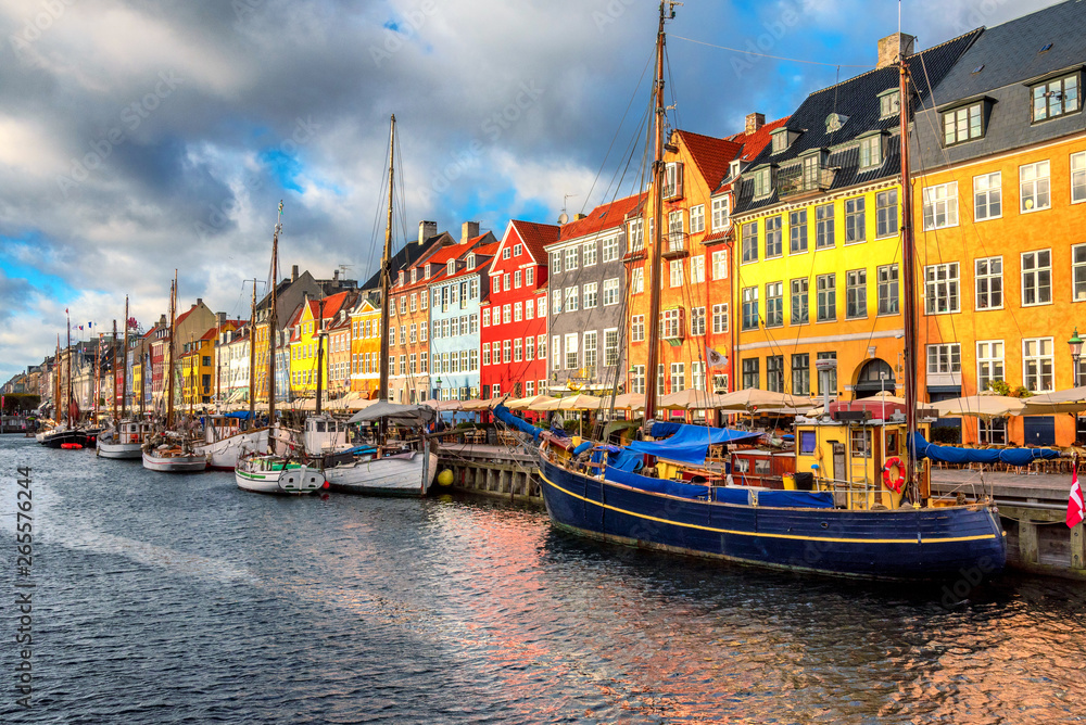 Fotografia  Nyhavn area of popular bar and restaurant at beautiful blue sky, with colorful facades of old houses and old ships in the Old Town of Copenhagen, capital of Denmark