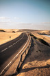 Long black way road in the desert with beautiful beach on the side - concept of travel and summer adventure alternative vacation in tropical beautiful scenic place - blue sky in background
