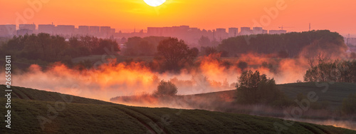 Foto auf Leinwand Koralle beautiful, misty sunrise over wavy green fields and small lakes-panorama