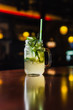 Refreshing summer lemonade with cucumber and rosemary in a glass jar at the bar with lights in the background