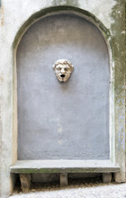 City Detail In Bergamo Alta, The Upper Town In Italy. A Stone Bench Under An Arch With A Sculpted Head As A Minimal Decoration
