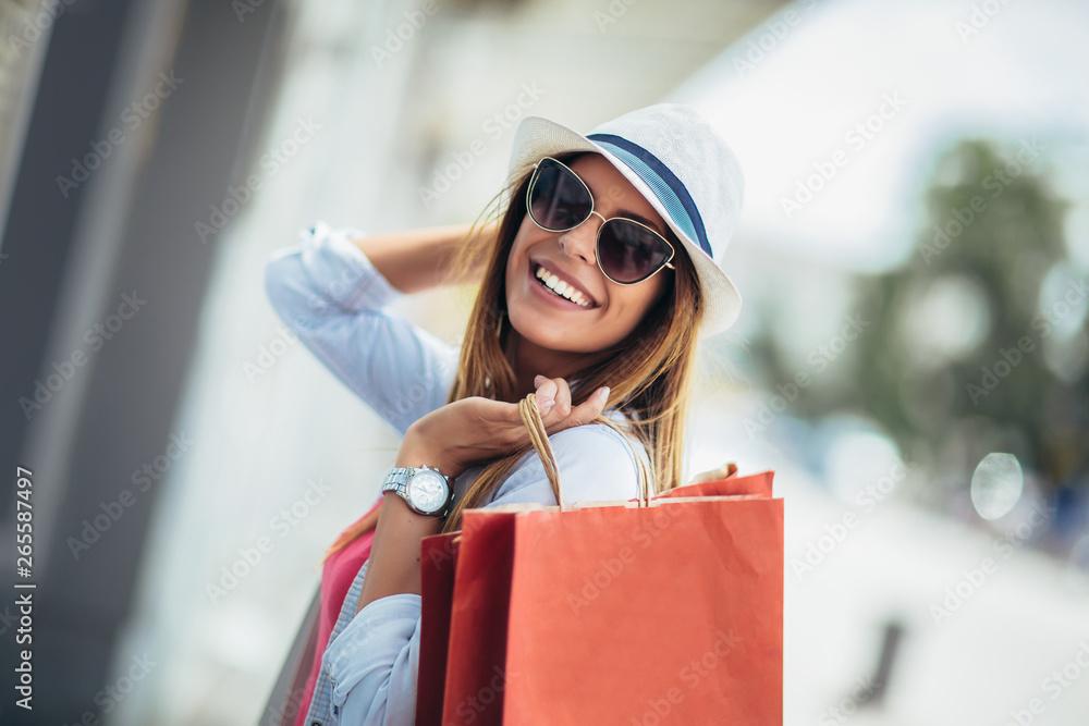 Fototapeta Beautiful woman holding shopping bags and smiling - outdoors