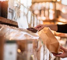 Seller's Hands Filling A Coffee Bag From A Bulk Dispenser