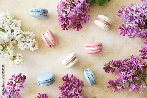Foto auf Leinwand Macarons Minimalistic composition with bunch of french macaron sweets of different color and taste, lilac flowerings scattered over yellow concrete texture background. Top view, close up, flat lay, copy space.