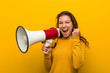 canvas print picture - Young european woman holding a megaphone cheering carefree and excited. Victory concept.