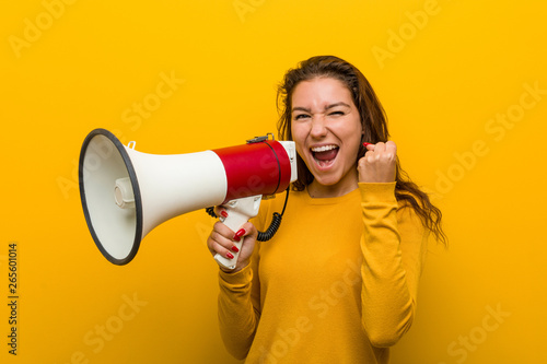 Young european woman holding a megaphone cheering carefree and excited. Victory concept. - 265601014