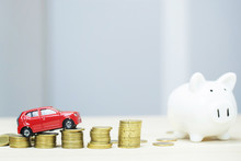Little Red Car Over A Lot Of Money Stacked Coins And Piggy Bank. Saving For  Bank Loans Costs Finance. Insurance, Buying Car Finance Concept. Buy And Pay By Installments Down Payment A Car. Soft Focus