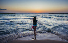 Girl Stands On A Seashore Against The Backdrop Of The Setting Sun In Tel Aviv, Israel