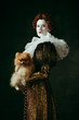 canvas print picture Brilliance view. Medieval redhead young woman in golden vintage clothing as a duchess holding puppy and standing on dark green background. Concept of comparison of eras, modernity and renaissance.