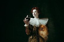 Wishes. Medieval Redhead Young Woman In Golden Vintage Clothing As A Duchess Holding Puppy And Glass With Red Wine On Dark Green Background. Concept Of Comparison Of Eras, Modernity And Renaissance.