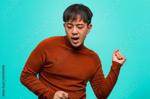 Fotomural  Young chinese man dancing and having fun