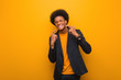 Young business african american man over an orange wall smiles, pointing mouth