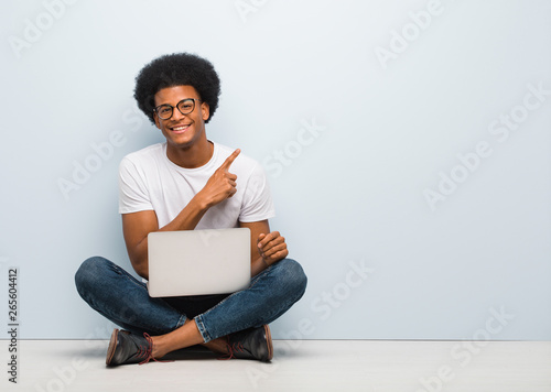Young black man sitting on the floor with a laptop smiling and pointing to the s Fototapeta