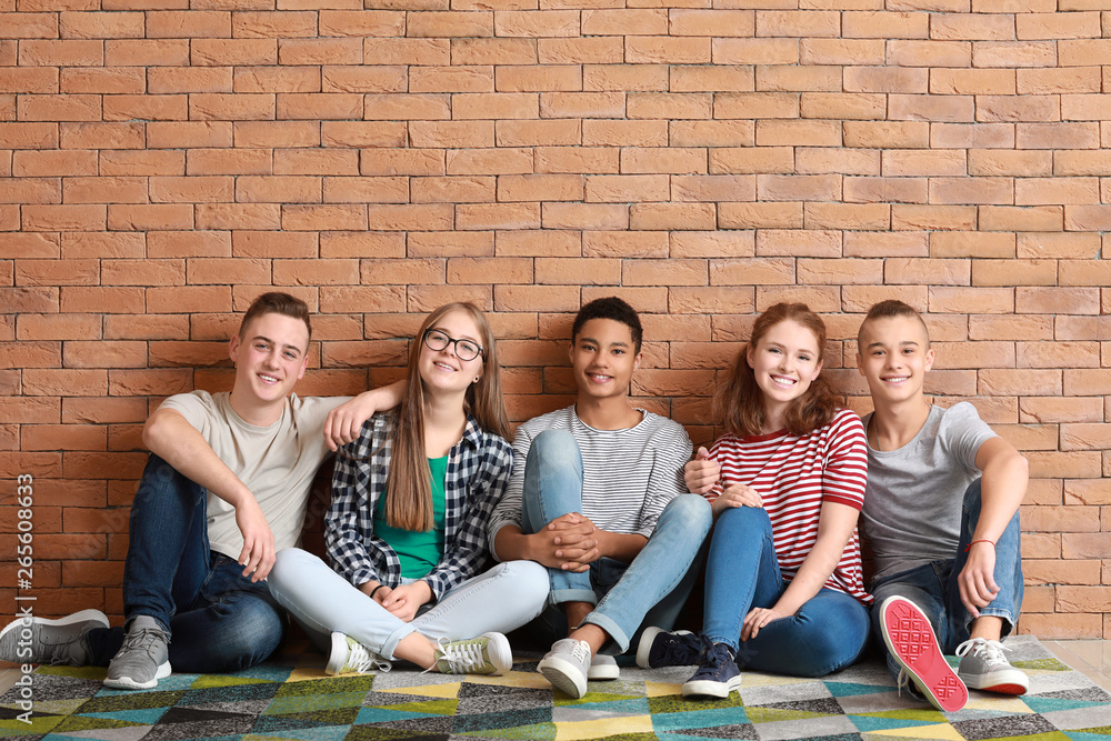 Fototapety, obrazy: Group of teenagers sitting on floor near brick wall