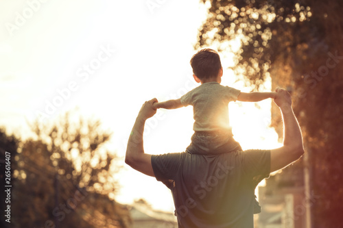 Happy family: Young father with his little child sitting on father's shoulders i Fototapeta