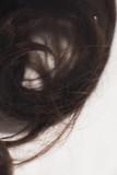 Detail of brown curly hair lying in water in sink. - 265617871