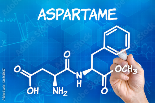 Photo Hand with pen drawing the chemical formula of aspartame