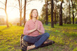 Beautiful young woman sitting in a pose of a lotus on city park sunset background. Practice meditation, kundalini yoga. Female eyes closed and open energy chakras.